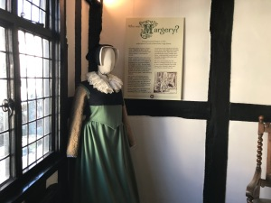 """Image shows a mannequin wearing a Tudor style green gown, black kirtle, white ruff and black coif, stood in front of a display board entitled """"Who is Margery?""""."""